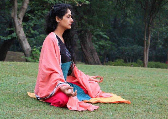 Rupinder Kaur meditates in a grassy field