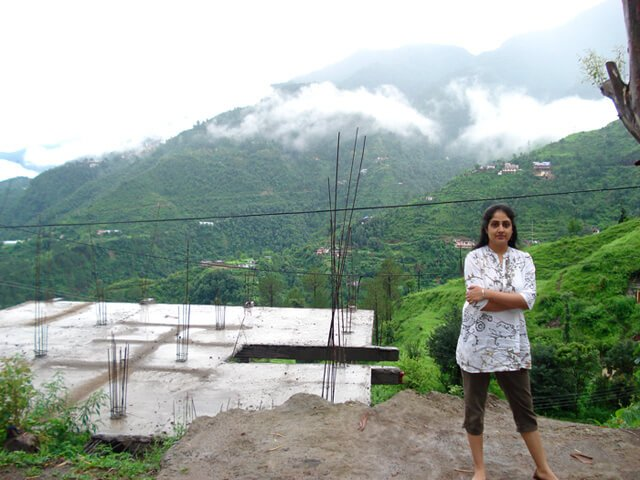 Rupinder Kaur stands with arms folded at the foot of a mountain