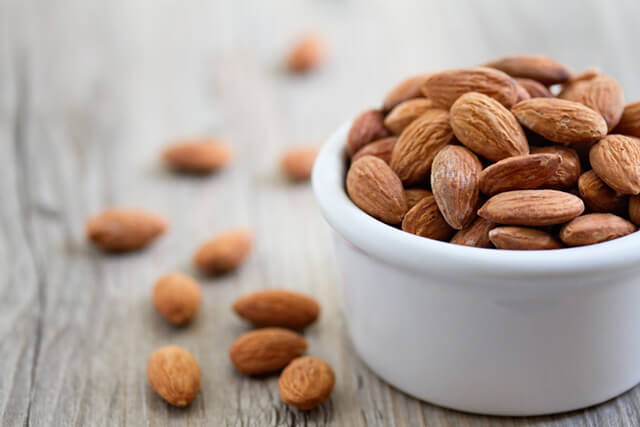 Almonds spill out of a porcelein bowl