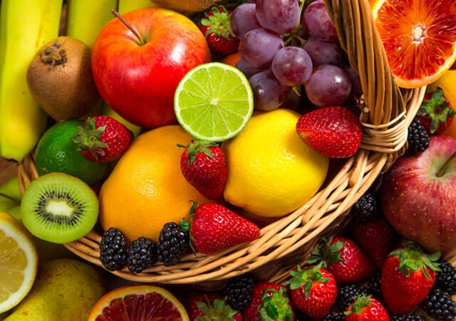 A basket teems over with colorful fruits