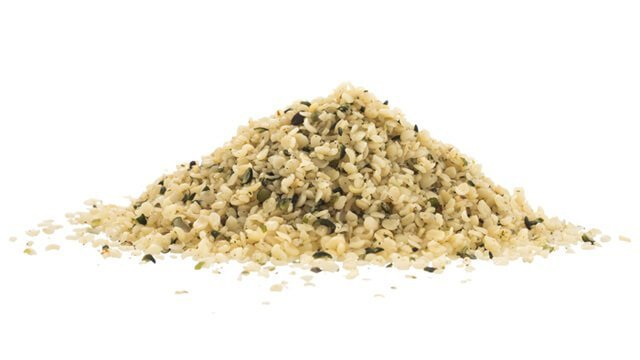Hulled hemp seeds on white background