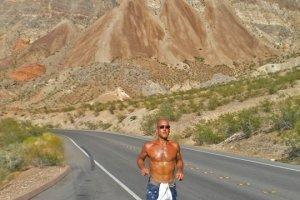 Jeff Sekerak runs along a road by Lake Mead