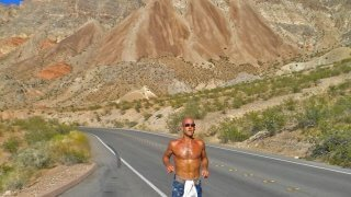 Jeff Sekerak runs along a road by Lake Mead