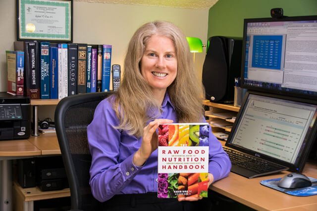 Karin Dina holds up a copy of The Raw Food Nutrition Handbook