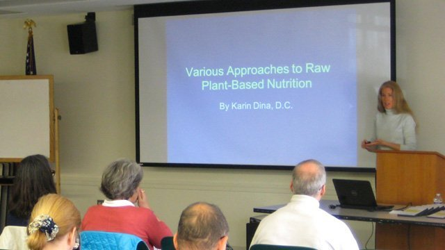 Karin Dina instructs on a raw food diet before an audience