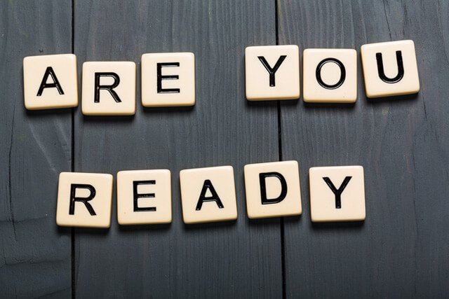 "Block letters spell out ""Are you ready"" on a table"