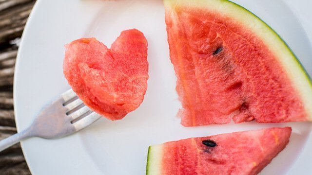 A fork in a heart-shaped watermelon piece on a plate