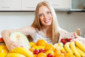 A woman behind a spread of fruits