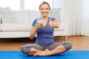 A woman signals thumbs-up while enjoying a green smoothie