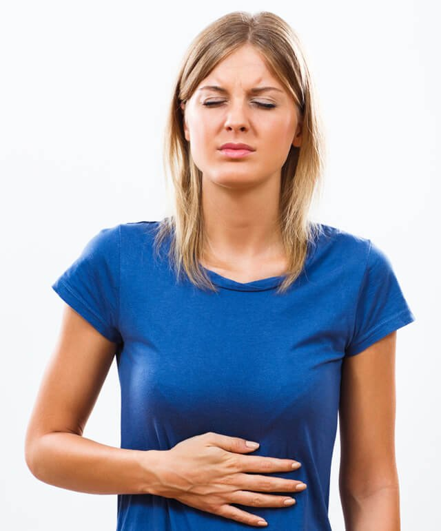 A woman with a stomachache rubs her belly
