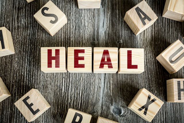 "Block letters spell out ""heal"" on a wooden background"