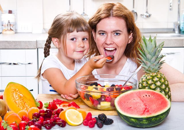 Daughter feeds mother from a bowl of fruits