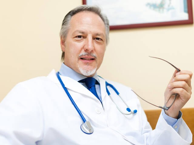 A doctor holds his glasses