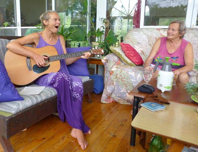 Kvetoslava Martinec plays a guitar in front of a guest