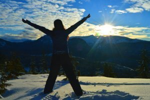 "Tarah Millen facing the sun while standing in snow and with arms raised in a ""V"""