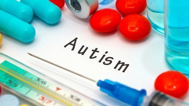 """Autism"" is written on paper next to needles and pills"