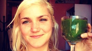 Anastasia Voss raises a green smoothie in a glass