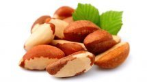 Brazil nuts with leaves on white background