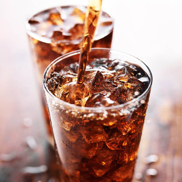 Cola is poured into a glass on a table