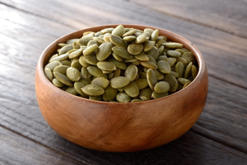 Pumpkin seeds in a wooden bowl on a table - Fruit-Powered