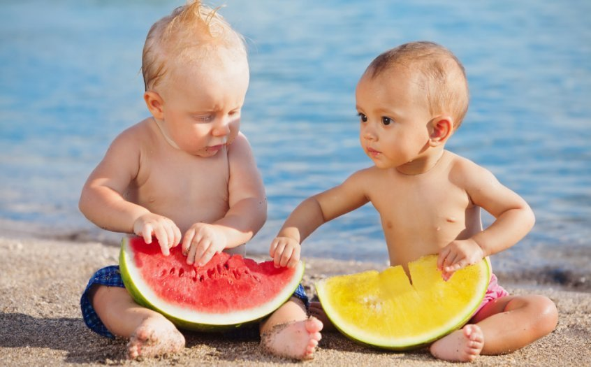 Two toddlers hold cut watermelon - food combining chart - food combining rules - Fruit-Powered