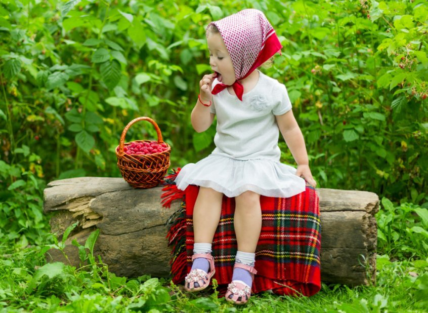 Young girl eats raspberries from a large basket - food combining chart - food combining rules - Fruit-Powered