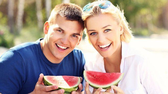 A man and woman hold watermelon slices on a beach