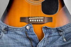 An acoustic guitar fit into a pair of women's jeans