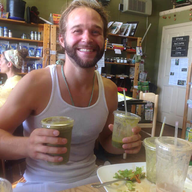 Drew Martin holds green smoothies at Arnold's Way