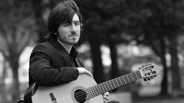 Francesco Barone sits outside with a guitar on his lap