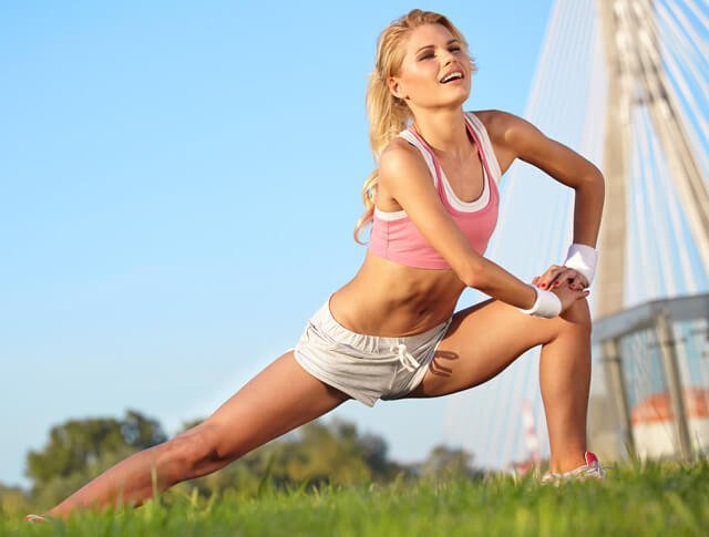 A blonde woman stretches outside