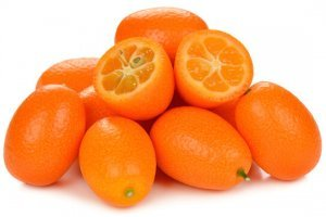 Whole and open kumquats on white background