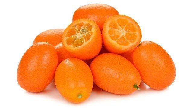 Whole and open kumquats on white background