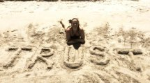 "Tasha Lee sitting beside the word ""Trust"" written in sand"