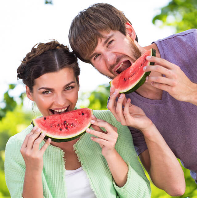 A woman and man eat watermelon slices outside