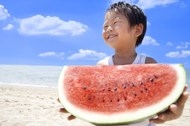 Asian boy eats watermelon on a beach