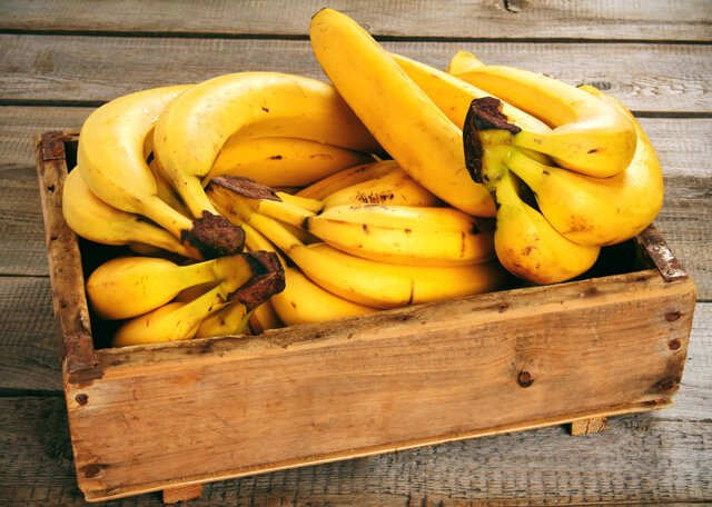 Bananas are stacked in a wooden crate