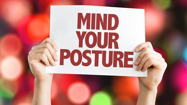 """Sign says """"Mind Your Posture"""" on background of lights"""