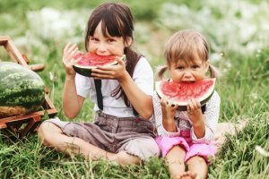 Young girls eat watermelon outside