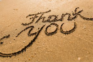 """""""Thank you"""" written in sand on a beach"""