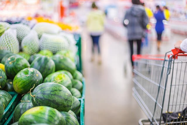 A shopping cart rests beside a mound of watermelon in a market