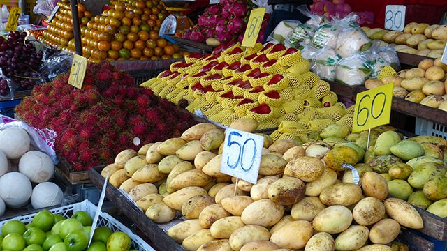 A fruit market features mangos and many other fruits