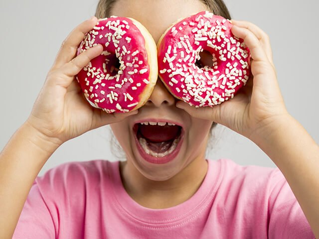A girl plays with doughnuts
