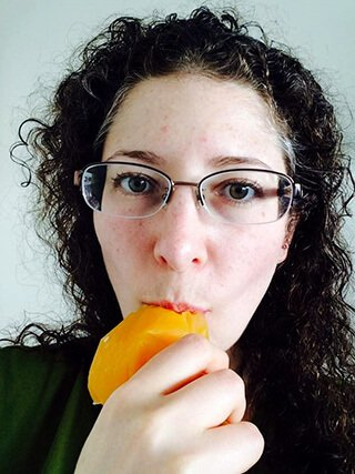 Rebecca Rosenberg eats a piece of fruit