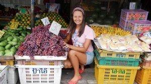Yulia Tarbath crouches at a fruit market