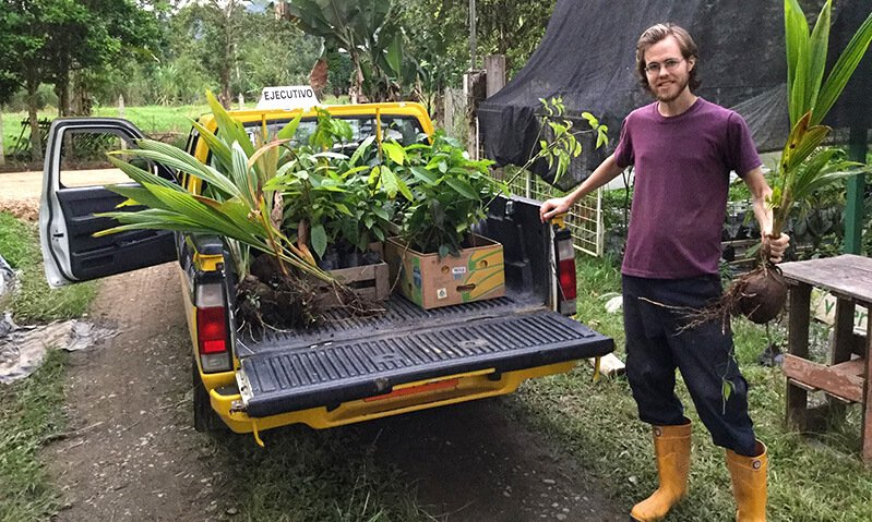 Peter Csere holds a plant while standing next to a truck