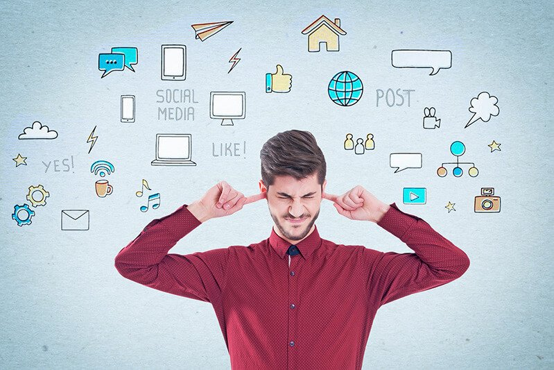 Stressed businessman covers his ears with social media icons around him