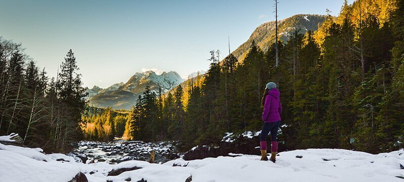 Tarah Millen stands on a snowy trail overlooking mountains