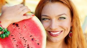 A woman rests a halved watermelon against her shoulder