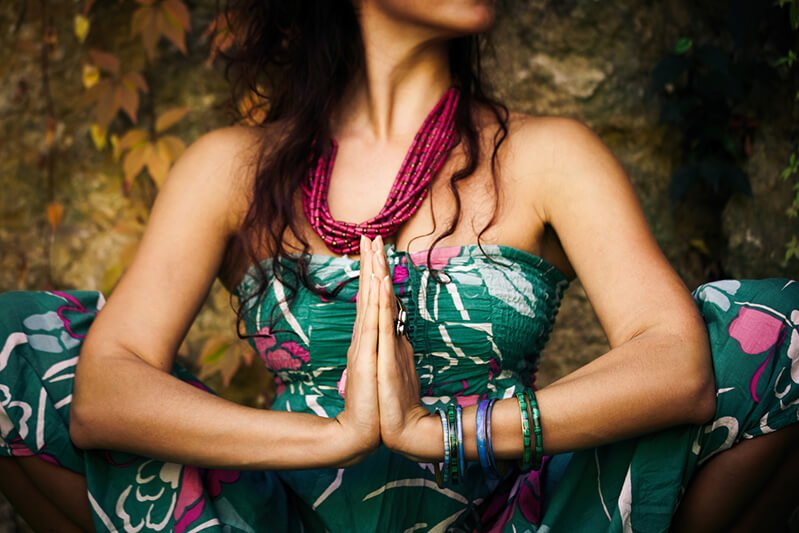 With hands closed, a woman practices yoga